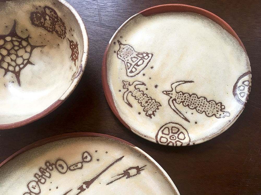 "detail of small bowl, 7"" & dinner plates in créme brûlée on red clay"