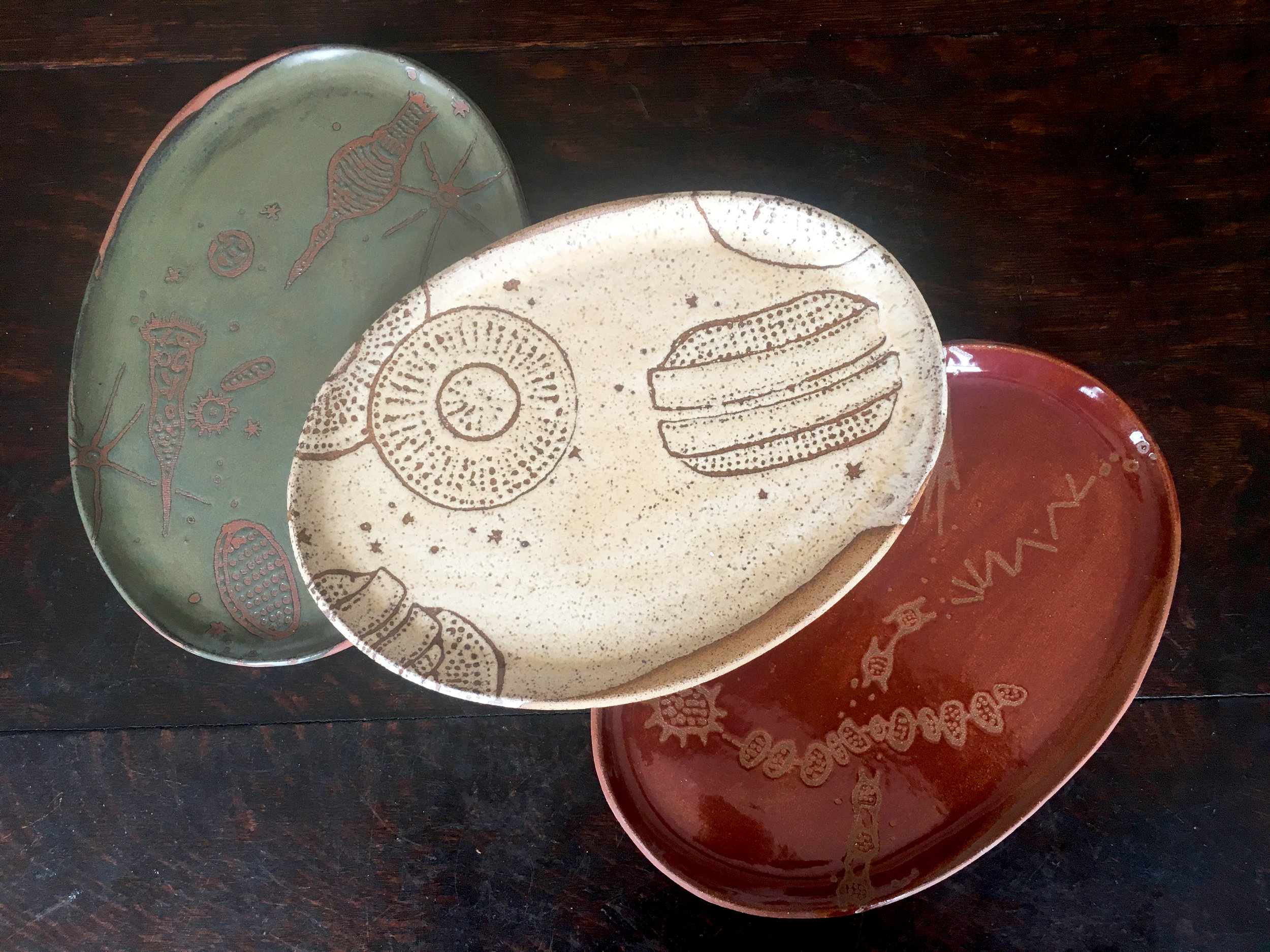 Platters are oval in small, medium & large with a wide rim on the grand platter   Trio in moss on red clay, créme brûlée on speckled clay & plum on red clay