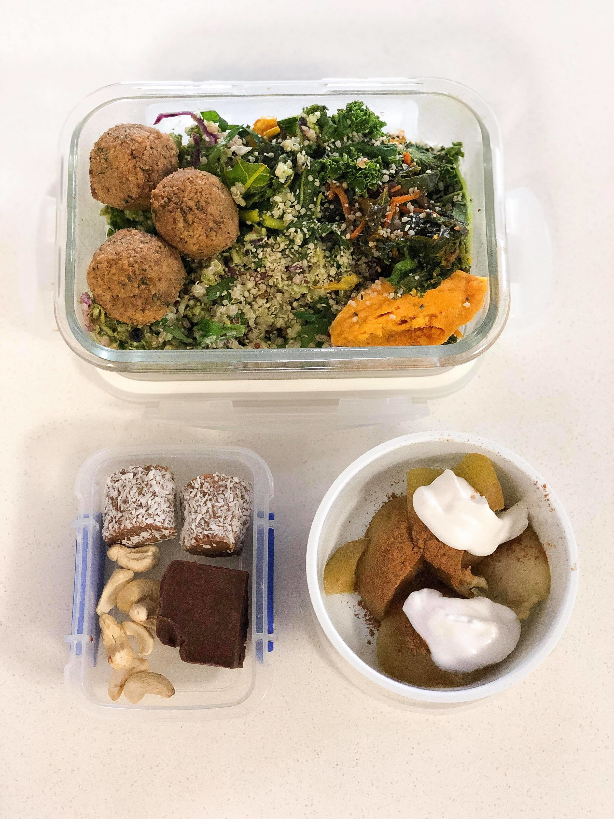 Healthy Lunch Box - 1. Hot Lunch. I have been making my Gut Bowl most days as my main meal. Doing that and adding a protein source (pictured is falafel), some gut lovin' products (here is My Hemple Hemp Seeds) and a fat source (I have carrot hummus in the bottom right hand of the container).2. Far left is my little snack box. Here I have some raw unsalted cashews, date and coconut rolls (health food store) and a slice of homemade Low Carb Choc Fudge).3. Far right is my stewed apple combo. I stew an apple in boiling water until soft. Then I cut away the core, add some ground cinnamon and top with Coconut Yoghurt.4. A few things that are missing.-I pack some protein powder (Prana Coconut Milk) to have with water during the day.-I make a coffee with me from Pod and Parcel and add some Bonsoy soy milk. When I get to work I'll warm this up and add some hot water.-My breakfast, dinner and pre-dinner snack are not pictured.