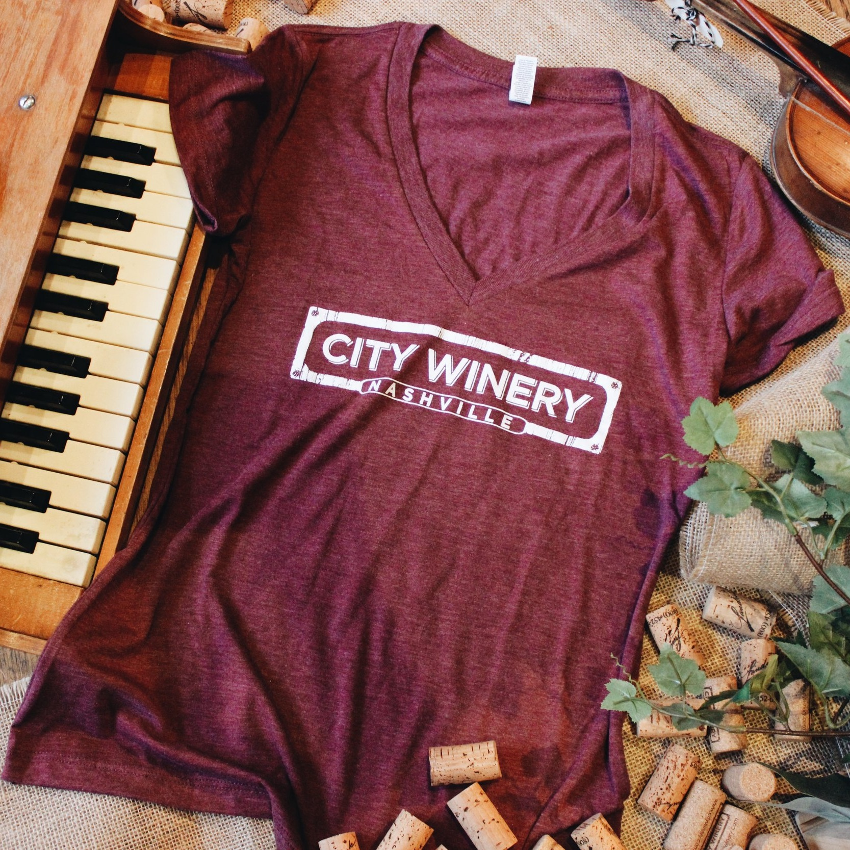 NASHVILLE LOGO RED WOMAN'S T-SHIRT - Rep your favorite location of the City Winery brand with this comfortable, relaxed cotton t-shirt with a v-neck, heather red color and short sleeves. Fits true to women's sizing.