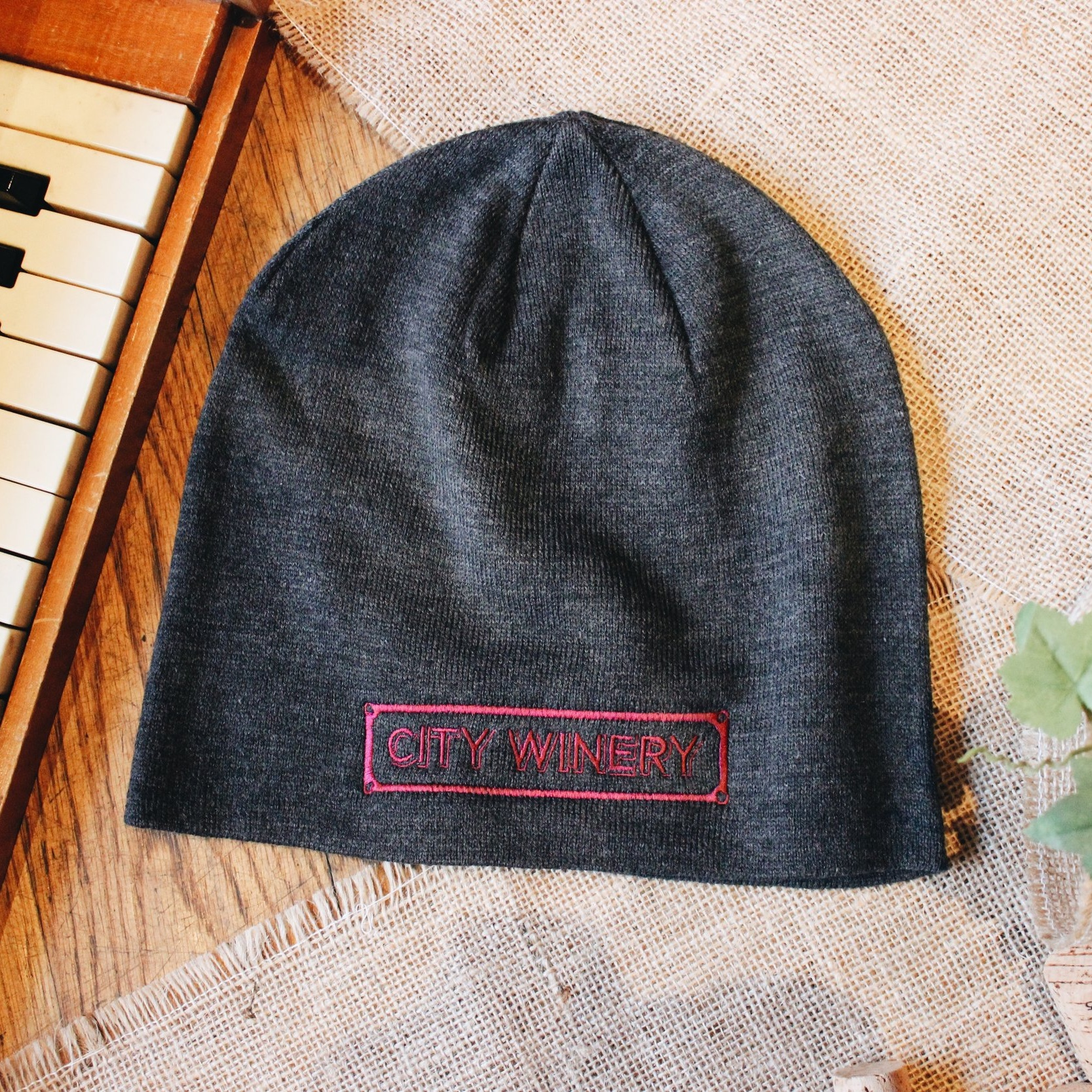 City Winery Logo Beanie - Rep the City Winery brand and keep your noggin warm with this comfortable, deep grey beanie with a wine red logo for yours truly. Fits true to adult sizing.