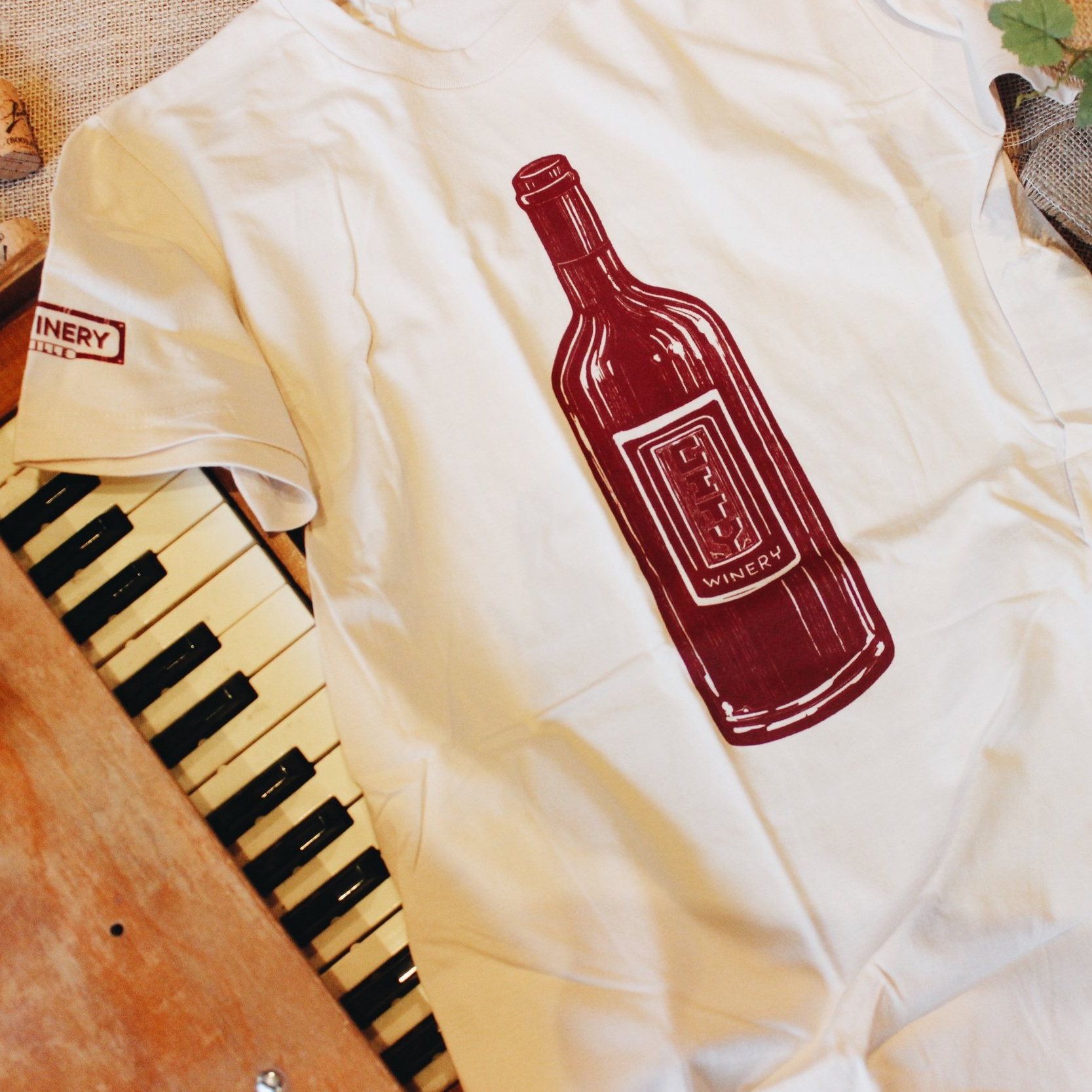 Isle of Printing Shirt - Sand - Our talented Pie Town neighbors at Isle of Printing and Bryce McCloud created this custom bottle imagery for City Winery Nashville's location when we launched in October of 2015. Now, the imagery can be seen throughout our lobby and lounge spaces, as well as on this stunning sand-colored t-shirt. Fits true to adult sizing.
