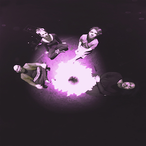 [Image: A shadowy background with four figures seen from above. They sit in a circle on a purple sphere. A white flower-like shape blooms between them.]