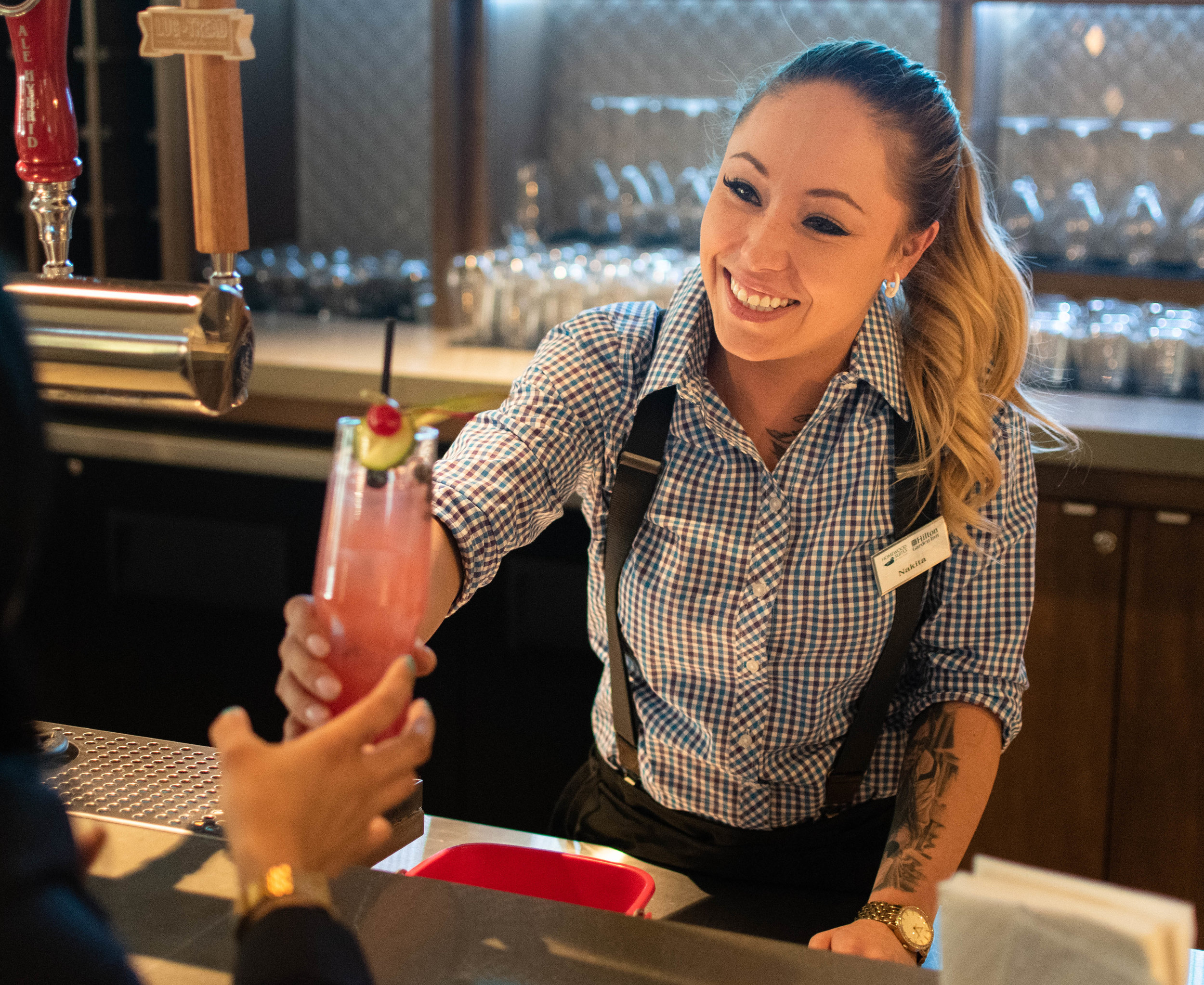 Women bartender smiling passing a drink to a customer