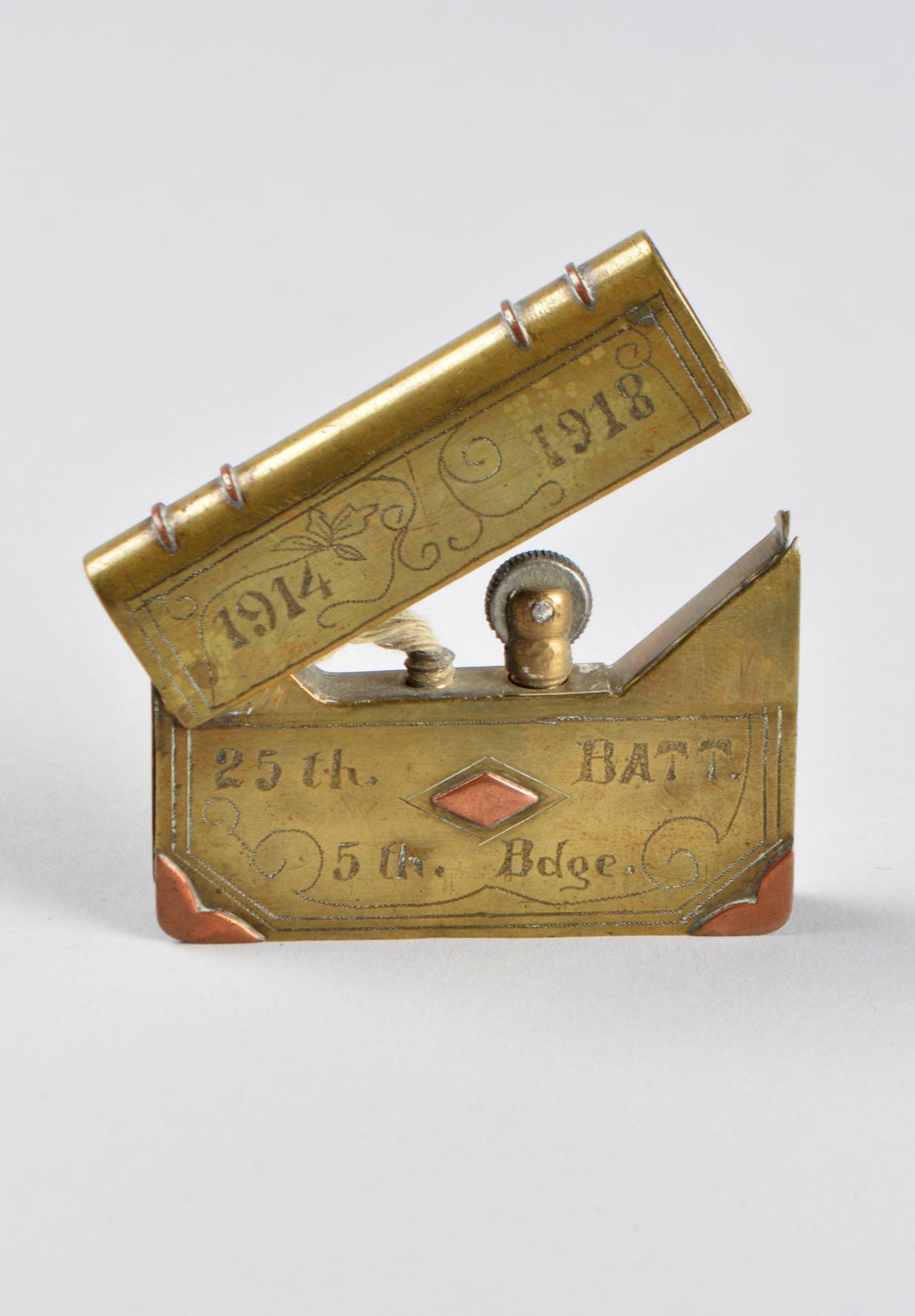 Lighter, brass, metal, cotton wick, 4.3 x 6.2 x 0.9 cm. Collection of Army Museum Halifax Citadel, Halifax, NS, XPE/88/1251. Photo: Gabriela García-Luna, Moose Jaw Museum & Art Gallery