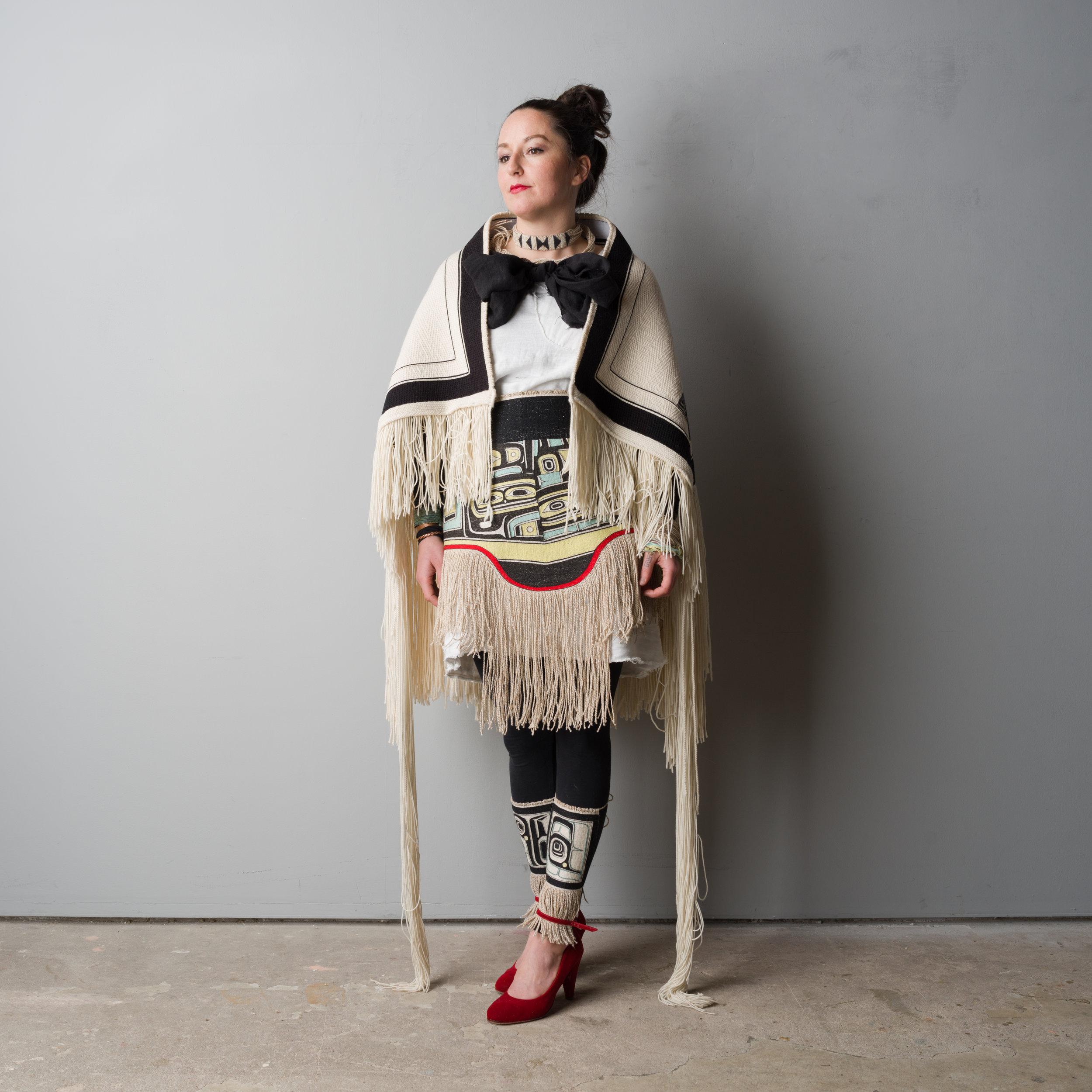 Exhibition catalog cover image for Interface: The Woven Artwork of Jaad Kuujus presented at Bill Reid Gallery of Northwest Coast Art September 19, 2018 – January 9, 2019. The artist Jaad Kuujus/Meghann O'Brien wears her handwoven Tlingit Raven's Tail Sky Blanket (2014. Merino wool, cashmere, mountain goat wool, 124.46cm x 132.08cm) and Haida apron The Spirit of Shape (2015–2018. Merino wool, cashmere, cedar bark, linen, 73.66cm x 38.1 cm).  Photo: David Koppe. Courtesy of the artist and Bill Reid Gallery of Northwest Coast Art, Vancouver, BC.