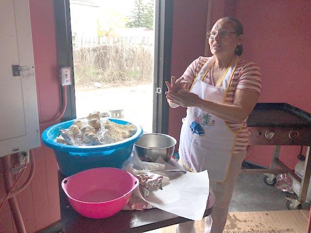 La señora Arminda Rosales haciendo pupusas para recaudar fondos para los gastos funerarios de Javier Ayala.