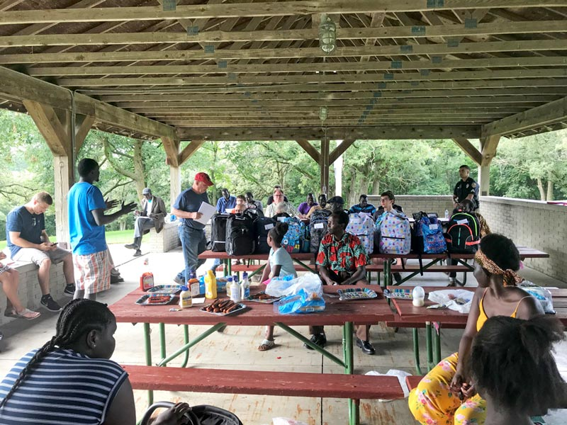 Nyok Kuoiloi lider de la comunidad de Denison se dirige a su comunidad para hablar acerca de la importancia de organizarse para formar parte integral de la comunidad. En la foto se pueden apreciar las mochilas donadas por Crawford County Memorial Hospital para los niños que están en edad escolar.
