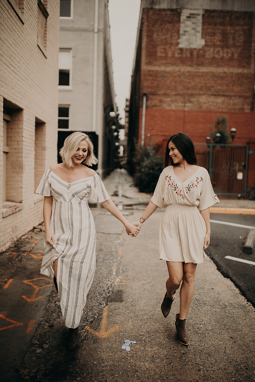2 Beautiful Girls in Feminine Dresses Holding Hands