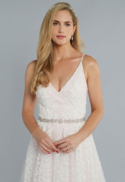 THE SOLSTICE - The epitome of romance and tenderness sum up the spirit of this special gown. Layers of soft white beaded satin give way to hints of blush and pink tones hidden underneath the abounding skirt. A delicate belt at the waist radiates femininity while the plunging neckline and flowing train beckon delight.