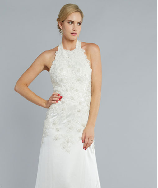THE ROSE - Classic and modern collide spectacularly to create this touchable flowing silk halter sheath gown. Wondrous beading and appliqués begin at the halter neck and float gracefully down to accentuate the waist and hips. A slight dusting train finishes this elegant dress made for the refined bride.