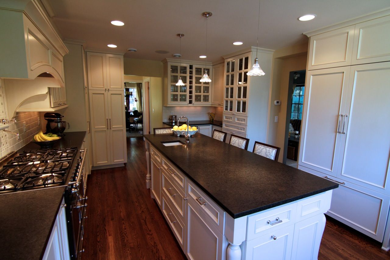 Kitchen remodel with large center island, wood floors, plenty of storage, hidden fridge, and new back splash.