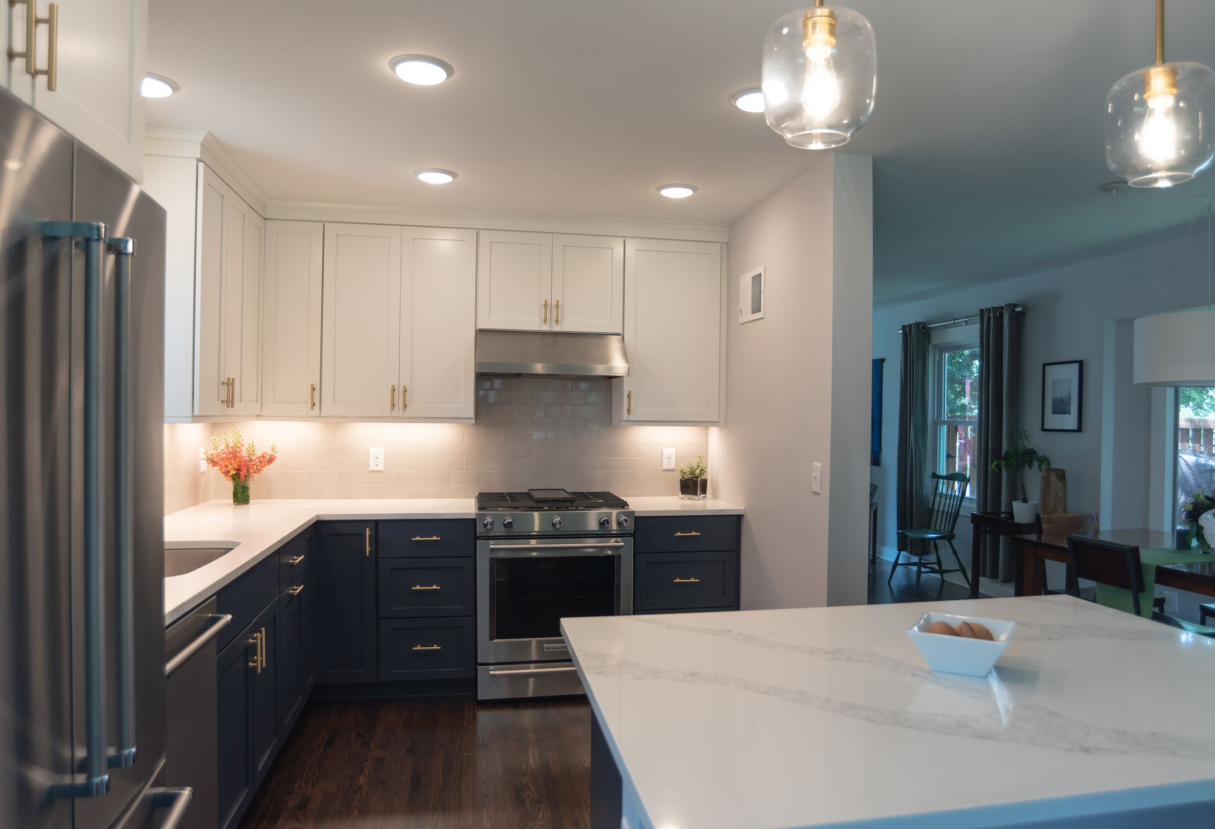 Kitchen remodel with large center island, blue lowers, white uppers, new wood flooring, and new appliances.
