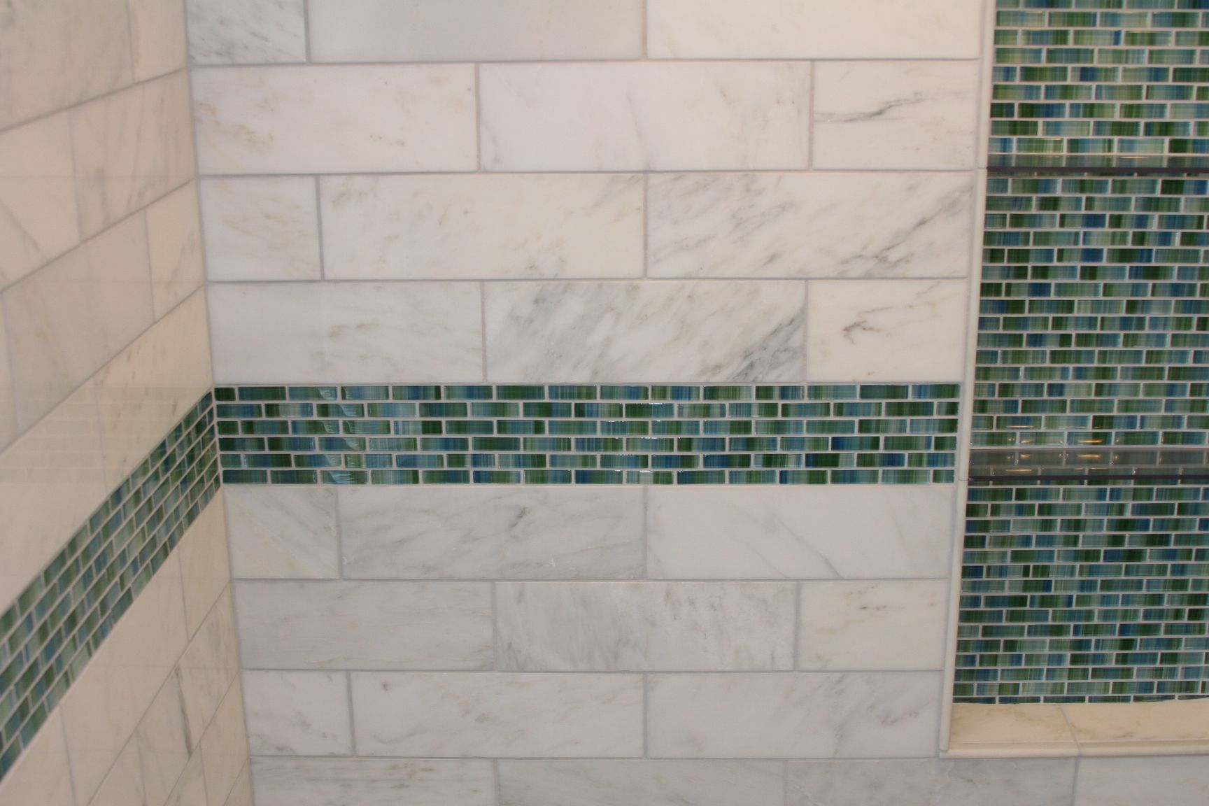 Bathroom remodel shower tile with teal accent tile stripe and niche.