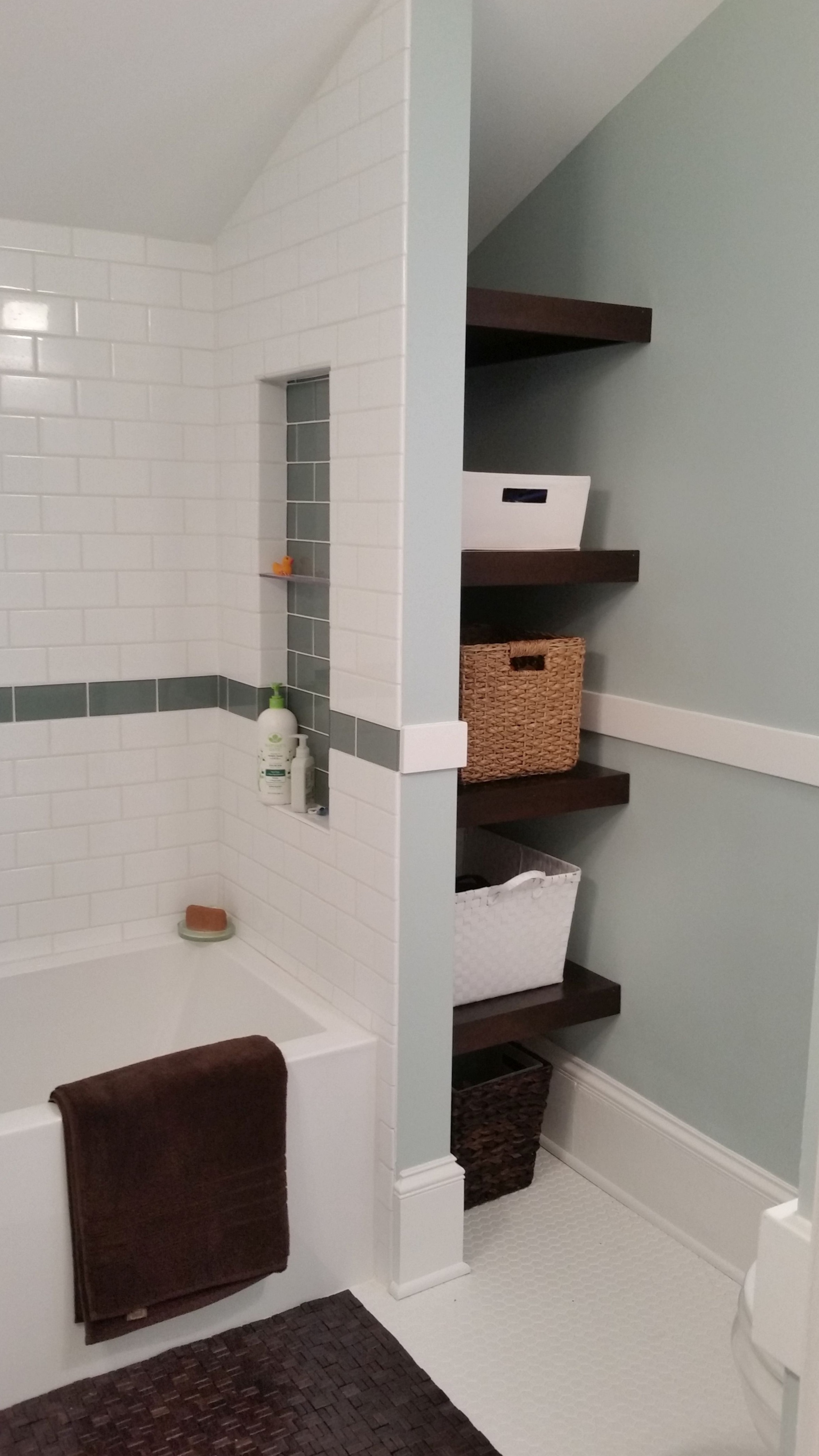 Bathroom remodel with dormer, new tub and shower tile, built in storage shelves, and fresh paint.
