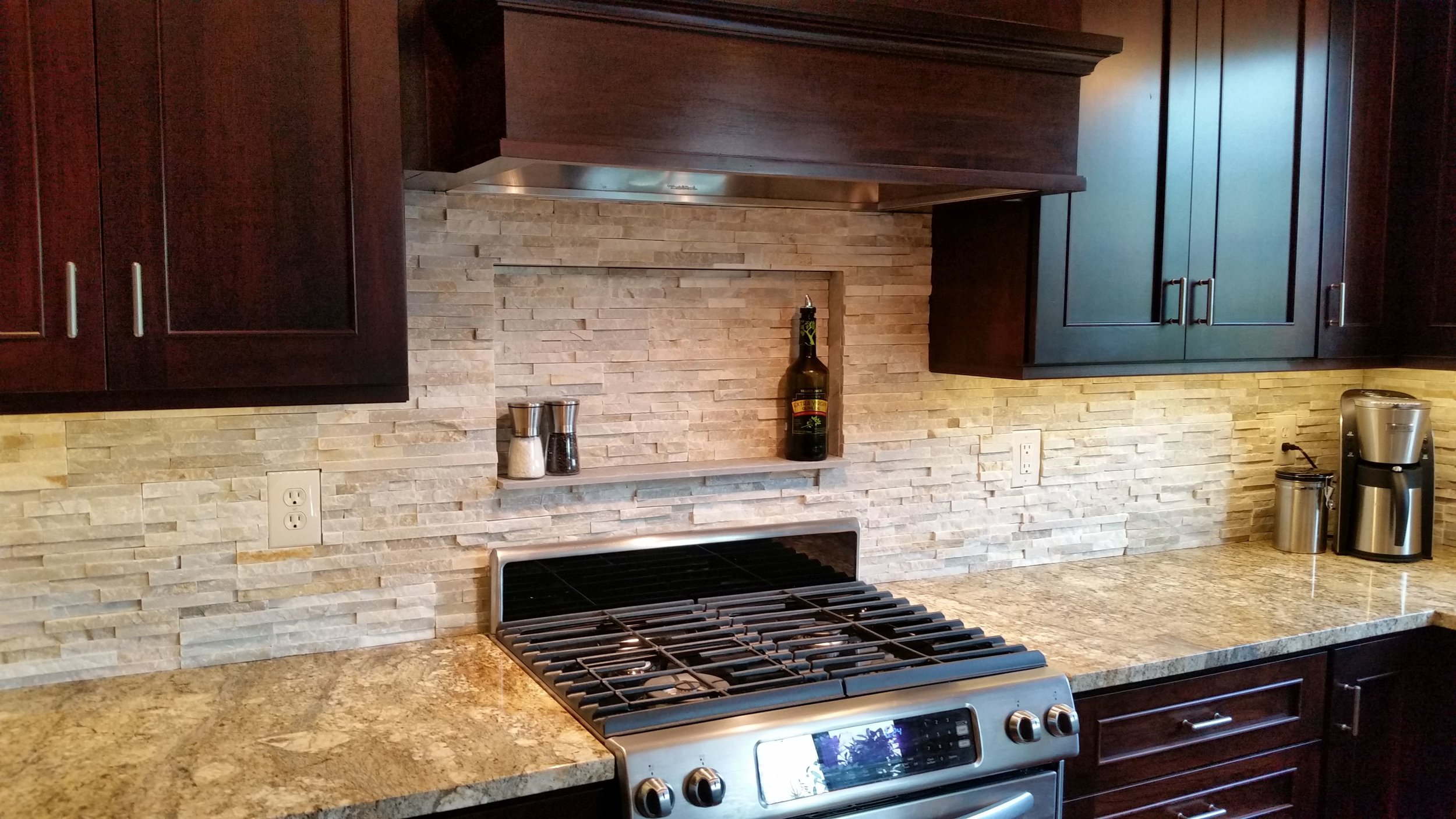 New kitchen remodel with new appliances, back splash, counter tops, cabinets, and more. Stove view.
