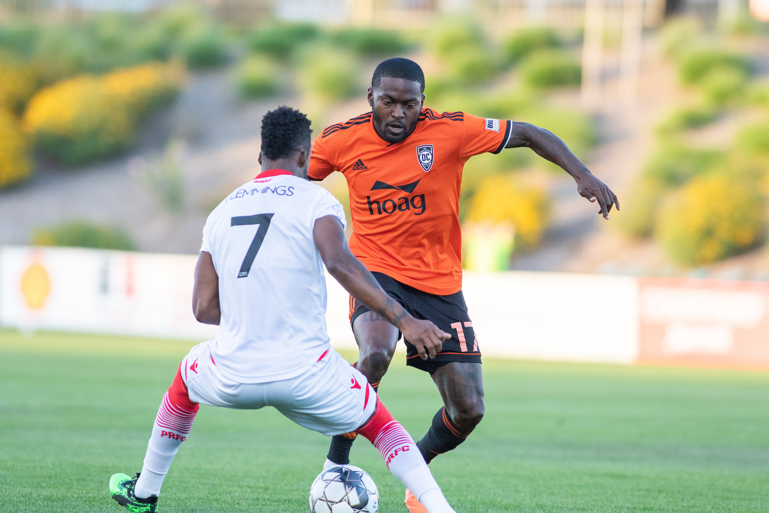 Orange County SC's Darwin Jones looks to dribble past Phoenix Rising FC's Junior Flemmings in their 2-1 victory on Saturday night.  |   Photo courtesy of Orange County SC (Liza Rosales)