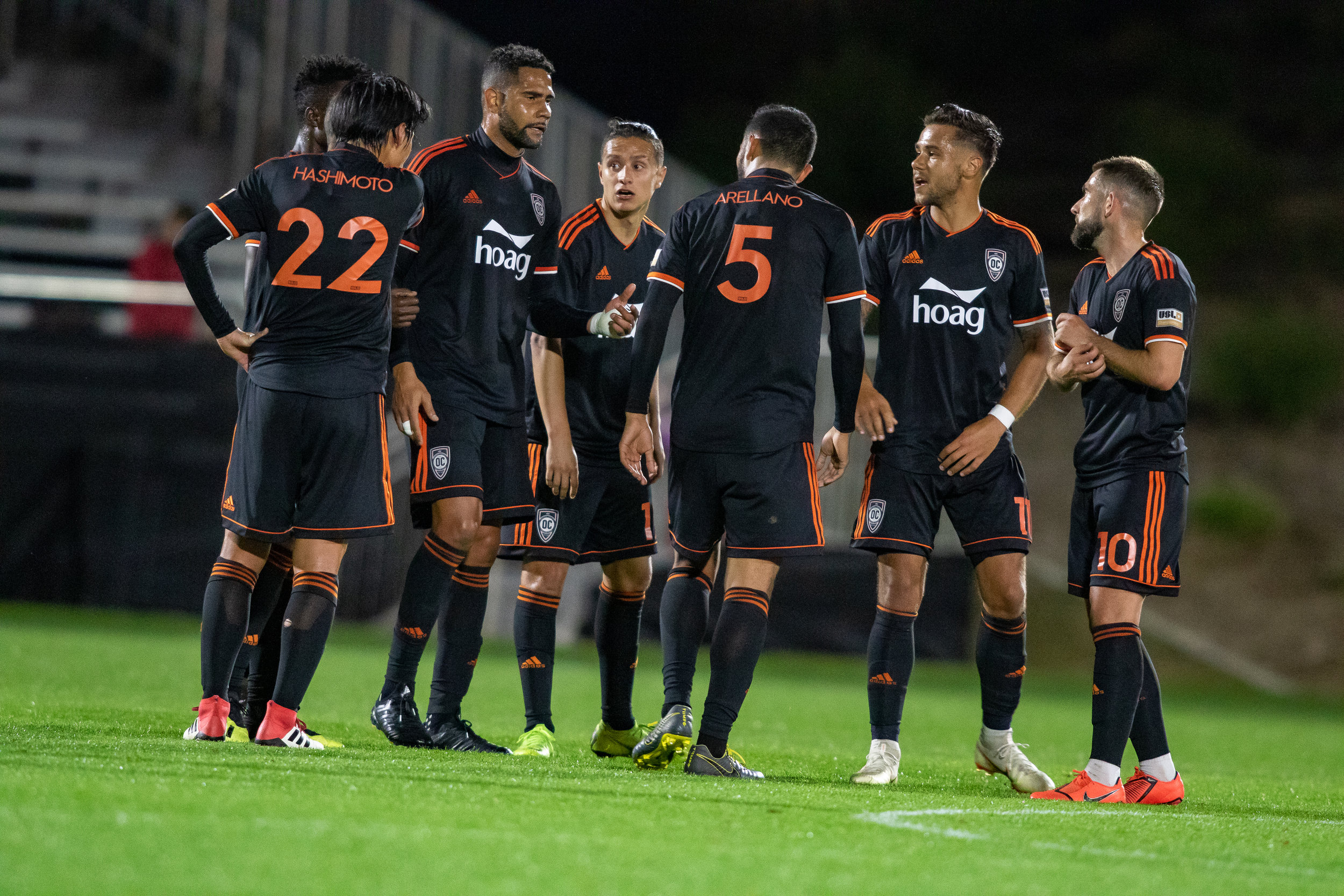 Orange County SC players Leonardo, Harry Forrester and others discuss their strategy during a match against New Mexico United.  |   Photo courtesy of Orange County SC/Liza Rosales