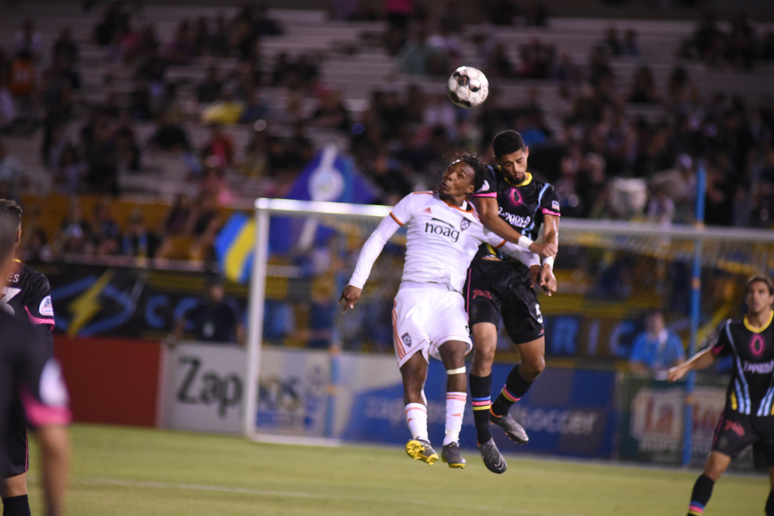 Orange County SC forward Michael Seaton battles Las Vegas Lights FC defender Javan Torre in the air. |  Photo courtesy of Las Vegas Lights FC