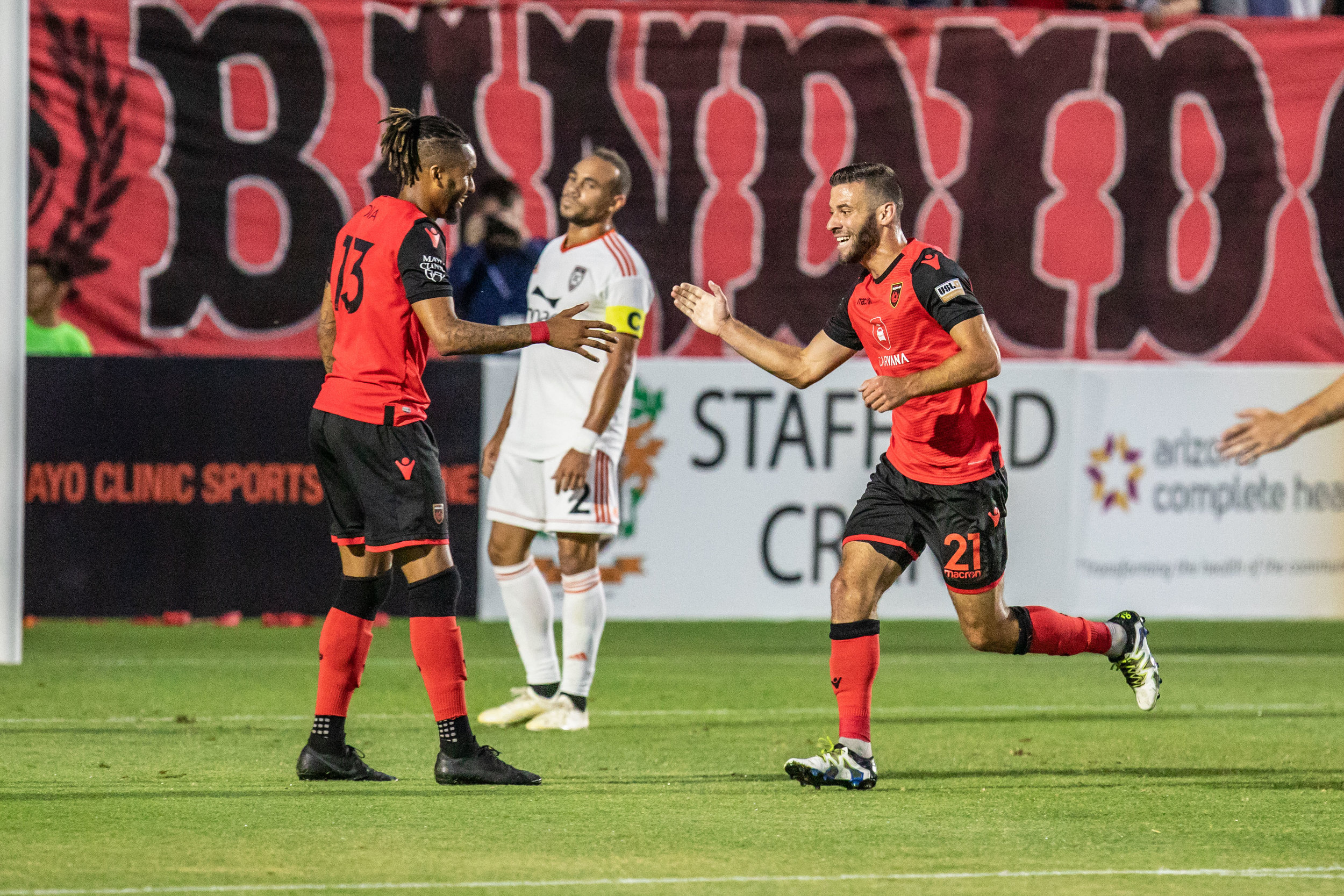 Orange County SC captain Kevin Alston looks on as Phoenix Rising FC's Amadou Dia and Joey Calistri celebrate in OC's 0-3 loss to Phoenix. |  Photo courtesy of Michael Rincon/PHXRisingFC.com