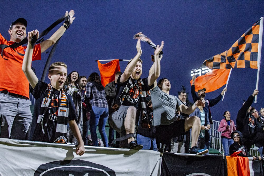 County Line Coalition founder Blaine Jenks leads the supporters group in a chant at Championship Soccer Stadium. | Photo courtesy of Orange County SC