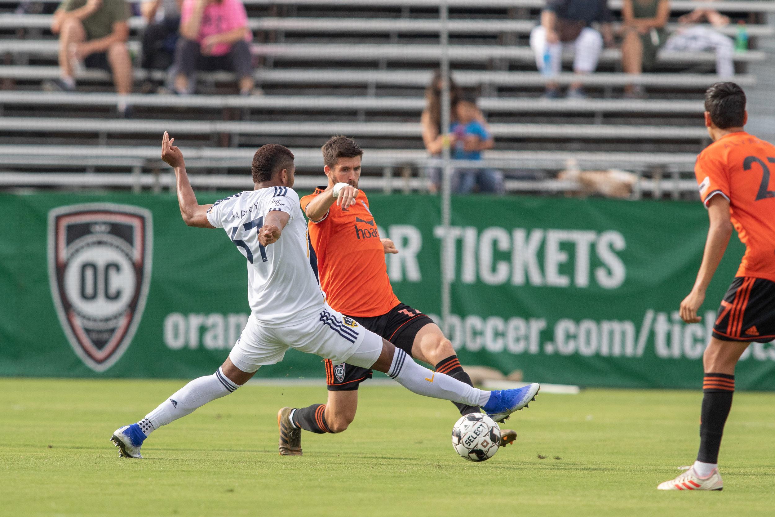 Orange County SC midfielder Aodhan Quinn attempts to get past LA Galaxy II midfielder Carlos Harvey.    Photo courtesy of Orange County SC/Liza Rosales