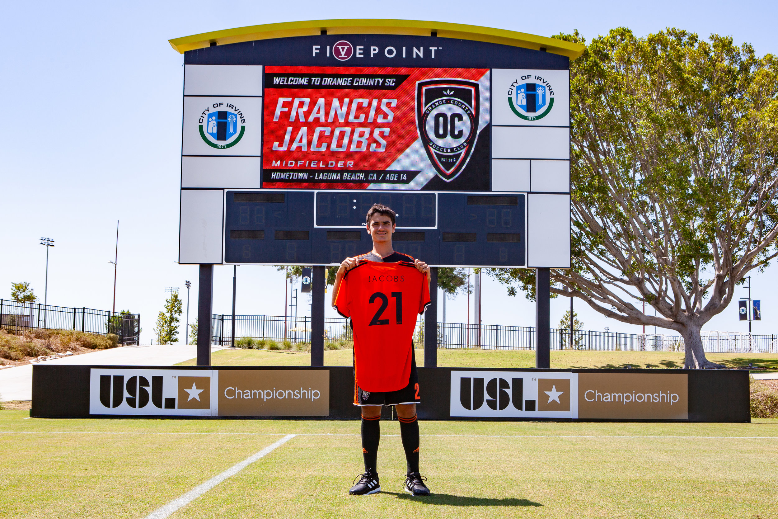 Newest Orange County SC midfielder Francis Jacobs shows off his number 21 jersey at his new home, Championship Soccer Stadium.  |   Photo courtesy of Orange County SC/Liza Rosales