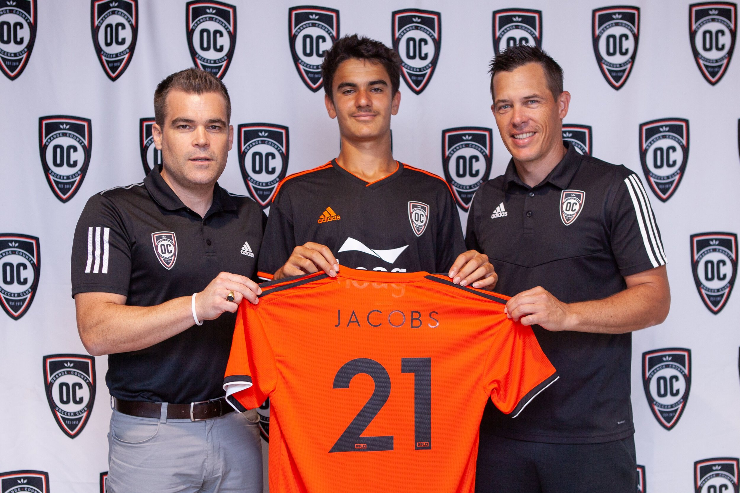 Orange County SC general manager Oliver Wyss and head coach Braeden Cloutier pose with the clubs newest signing, 14-year-old Francis Jacobs. |  Photo courtesy of Orange County SC