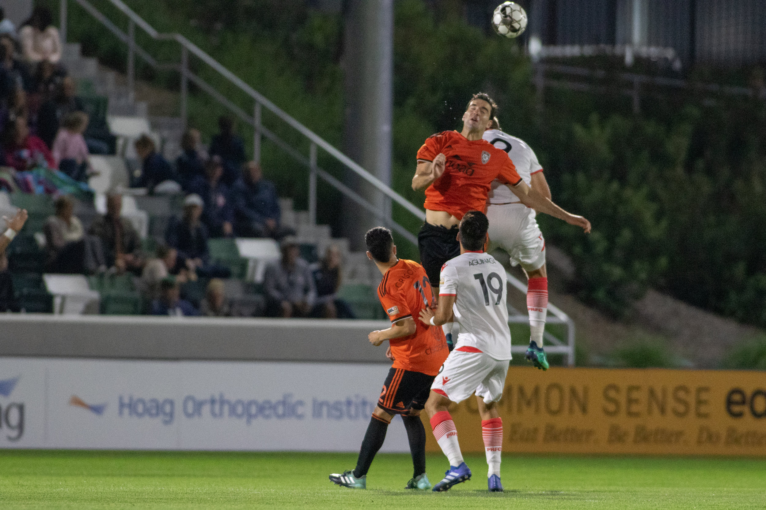 Walker Hume (right) using all of his height to clear a ball against Phoenix Rising FC in May. The center back will be tasked with knocking crosses down or putting them on frame on Sunday.  Photo courtesy of Liza Rosales/Orange County SC .