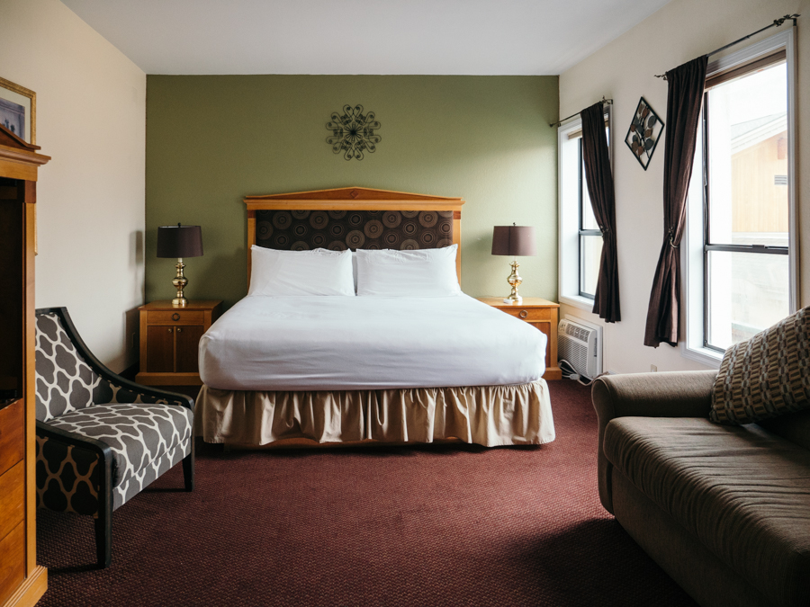 interior of adventure inn hotel room with queen bed and natural light
