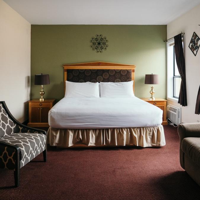 single queen bed in adventure inn hotel room