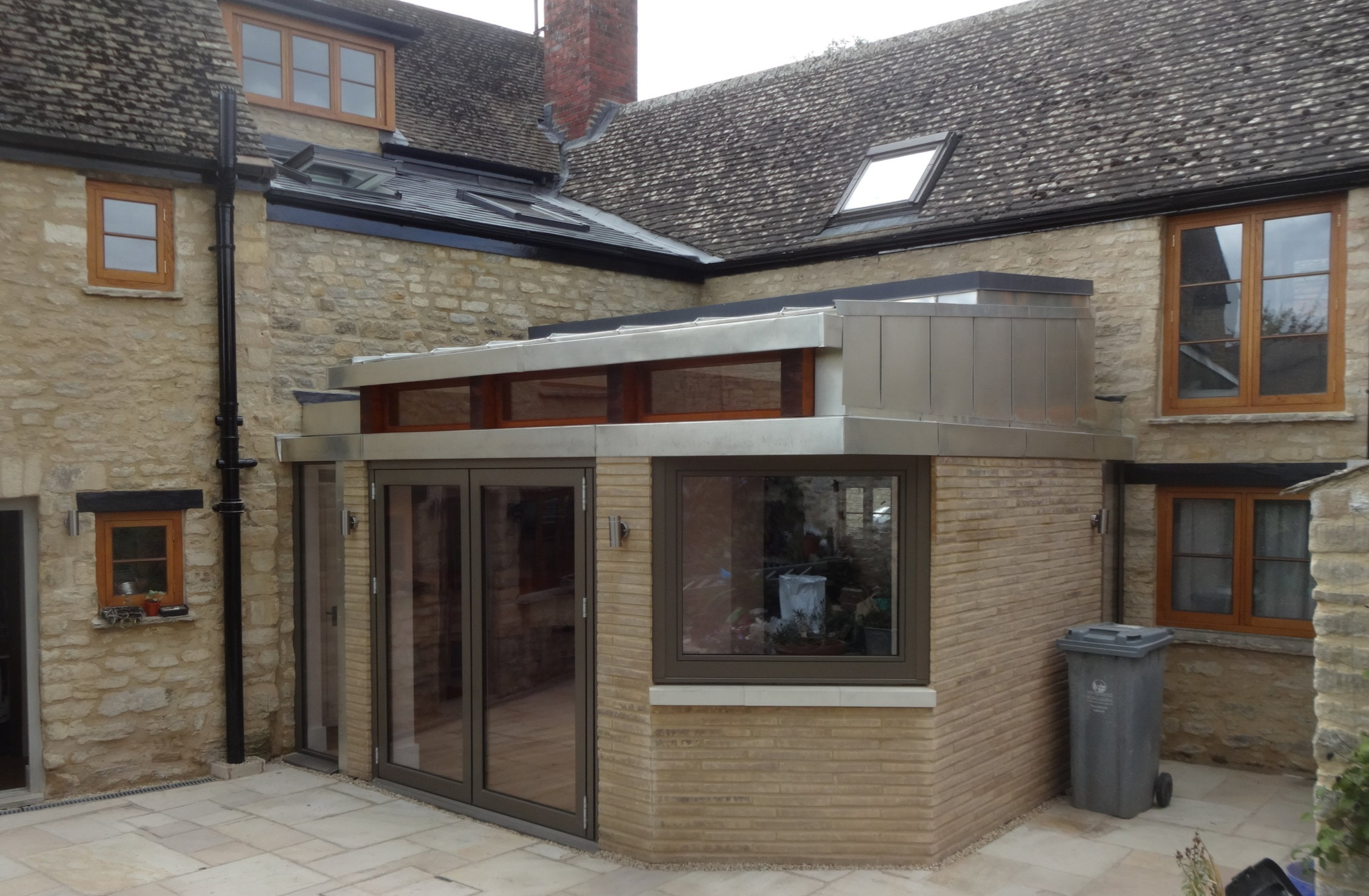 MALTSHOVEL HOUSE - This quirky extension uses both roofing and cladding details. The new look extension in Eynsham fits into a courtyard garden brilliantly against the old existing building.
