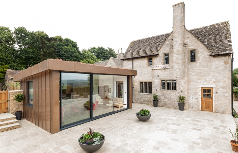 PRIVATE HOUSE GLOUCESTER - A large single story extension against a listed private house. Showing a contrast between old and new with the bronze finished copper.