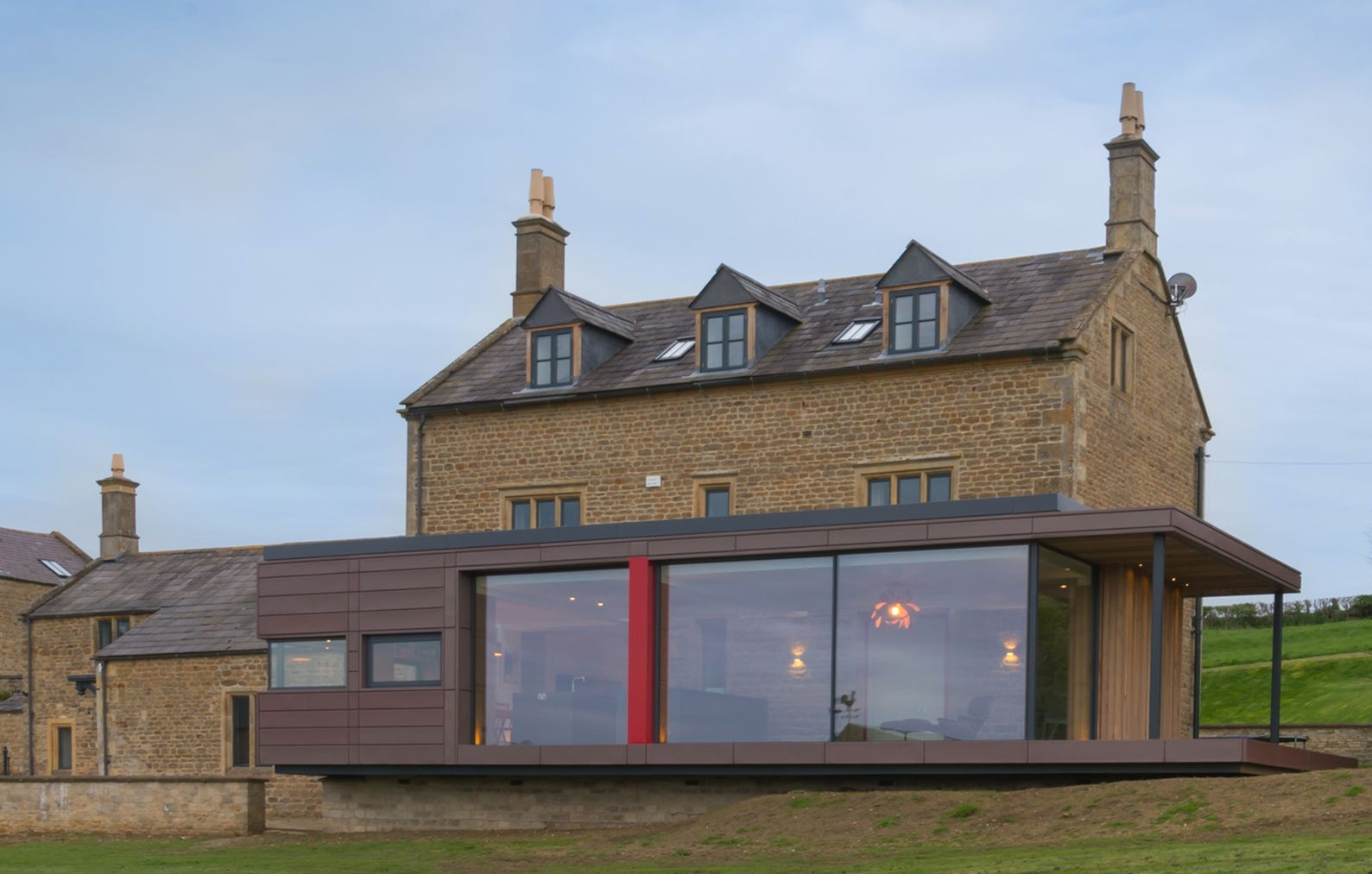 WARWICKSHIRE FARM HOUSE - This large single story extension also uses the red pigmento zinc. Sitting against the original listed building the coloured zinc interlocking panels allow for an ultra modern look.