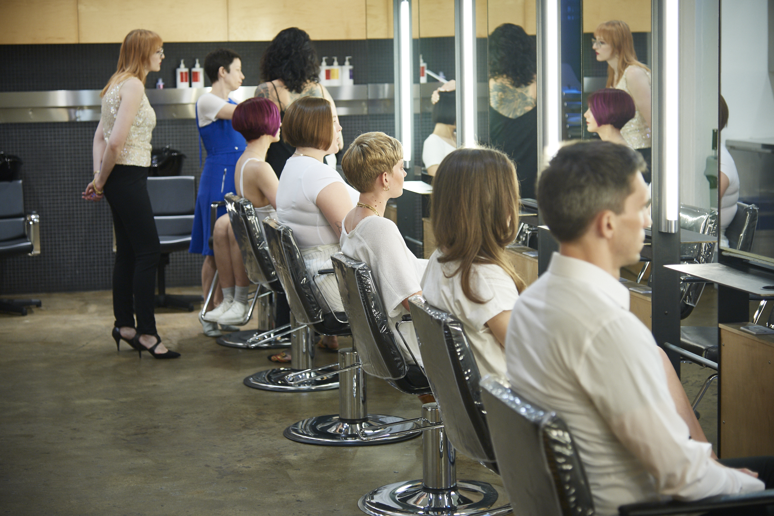 Lenny looks on as ARROJO master stylists check her presentation hair cuts with a fine tooth comb.