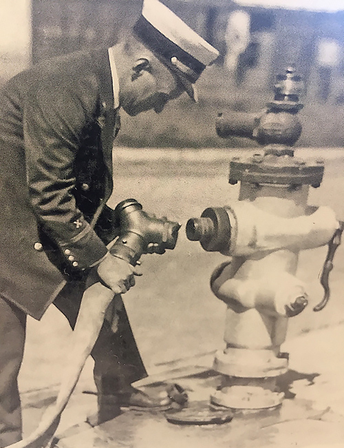 Pictured is Battalion Chief Harry Lucas demonstrating the hydrant fitting, the Lucas, he developed it for the Long Beach Fire Department in the late 1920's.