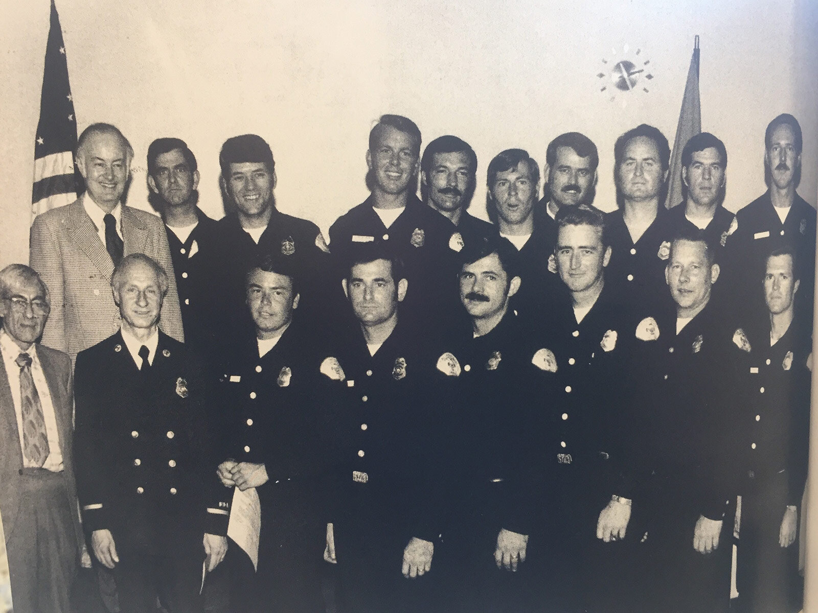 "The first Paramedic class is pictured here. From left to right: (first row) Dr. Irv Unger from Saint Mary's Hospital , Chief Rizzo, John Acosta, Art Santavicca, Gary Olson, Pat Highfill, Dennis Weller, and John Christensen; (second row) City Manager Bob Creighton, Bill ""Mad Dog"" Kelly, Walt Gupton, Don Aselin, Bob Shue, Craig ""Bird"" Vestermark, Bob Parkins, Gary Robertson, Dennis Wynn, and Carl Scheu."