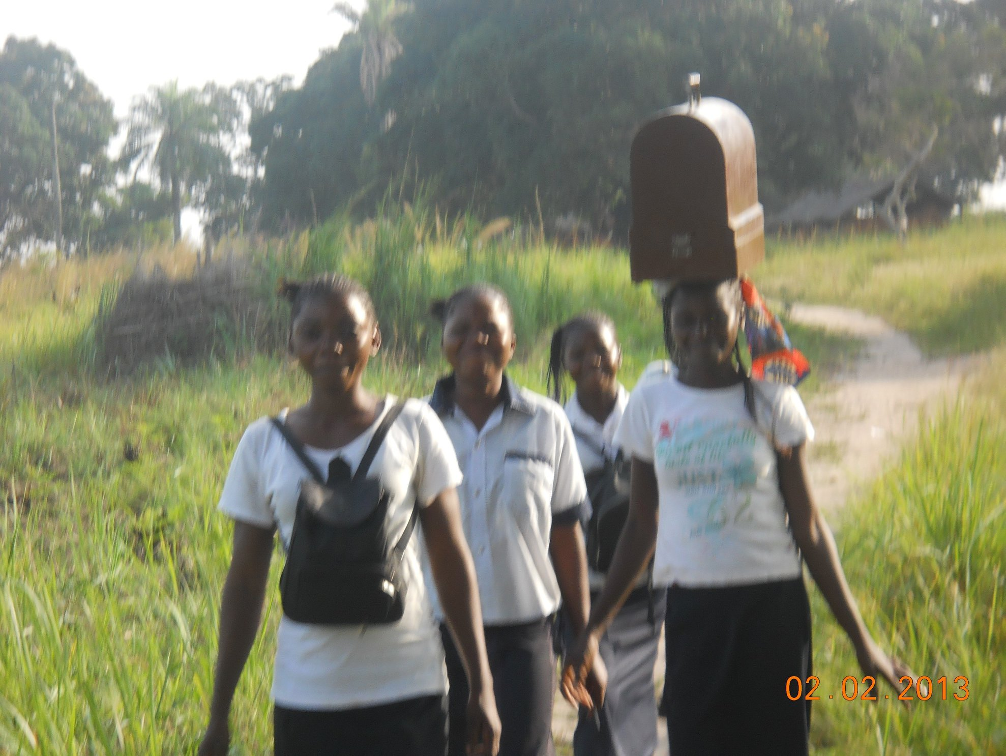 Before… A girl carries the school's only sewing machine for 50 girls on her head.