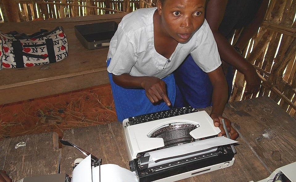 A student at Lycee Gina Gisanga learns for the first time how to use a typewriter.
