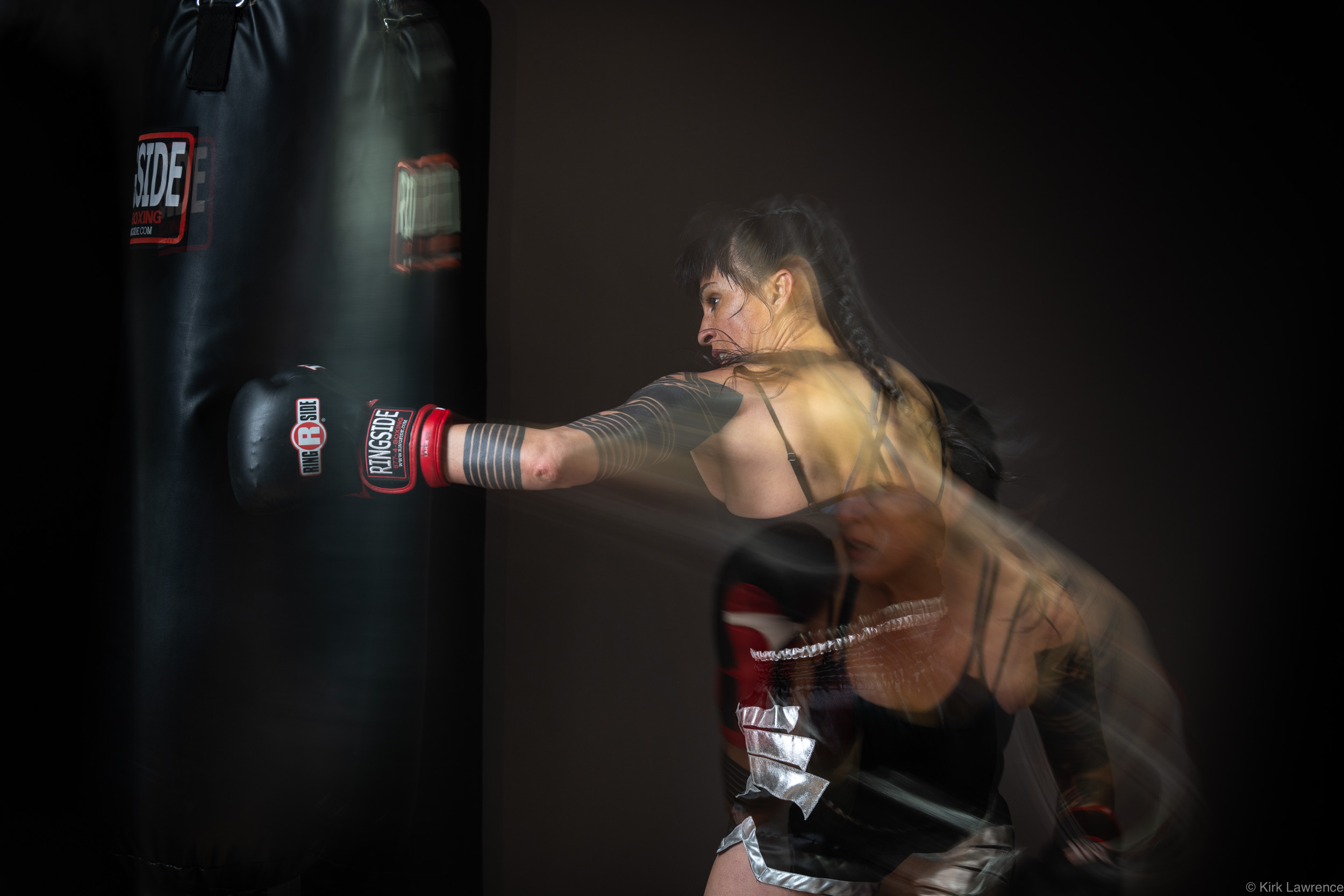 female_kickboxer_punching_bag_portrait.jpg