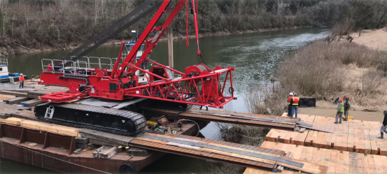 The 300-ton capacity crane crawls its way off the barge to the landing site
