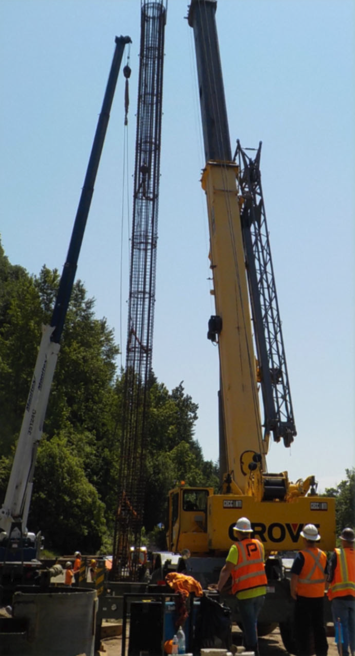 Crews pick up the rebar cage for placement in the drilled shaft for abutment 2 on the railroad side of the bridge.