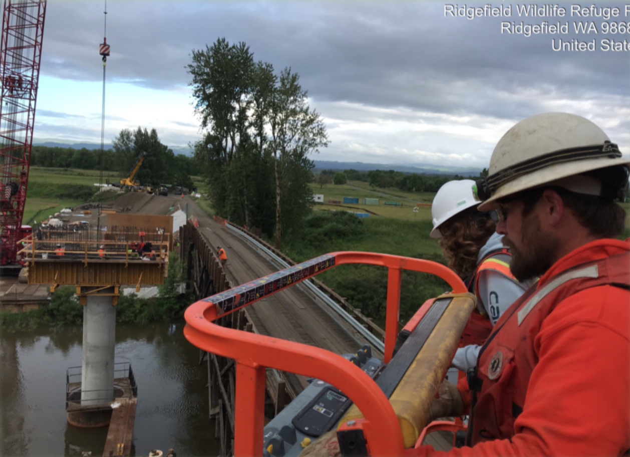 Representatives from FHWA and Ciccanti, Inc. use a lift to inspect rebar work on the pier caps.
