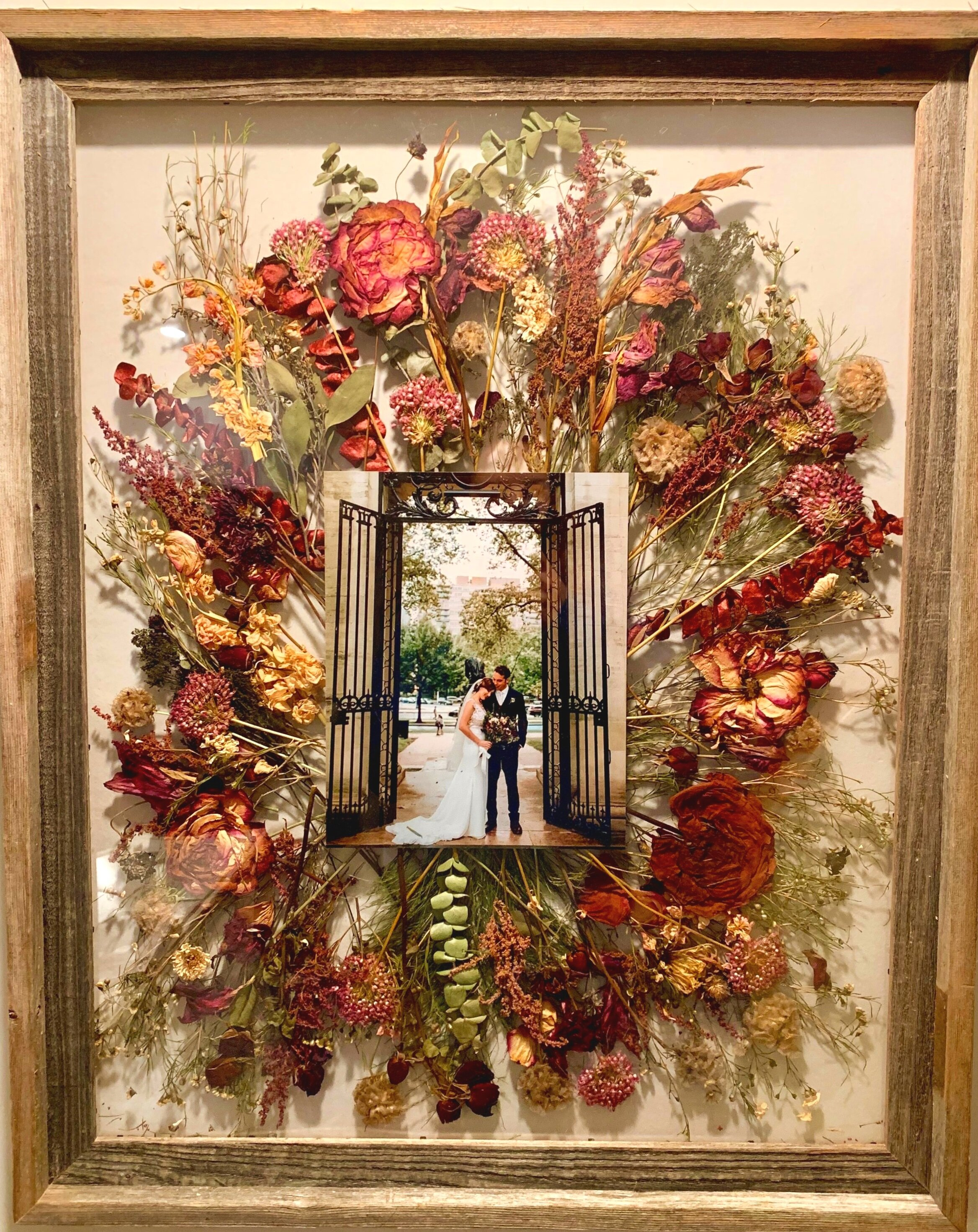 """Pressed bouquet from wedding. 24""""x 28"""" reclaimed barn wood frame with 8 x 10 print of bride and groom on the wedding day. Brides can deliver bouquets, invitations, photos, swatches of dress fabric, etc to be preserved in a frame or hanging shadowbox. See  Contact Page  to inquire about preserving flowers from weddings, proms, recitals, engagements, funerals, etc."""