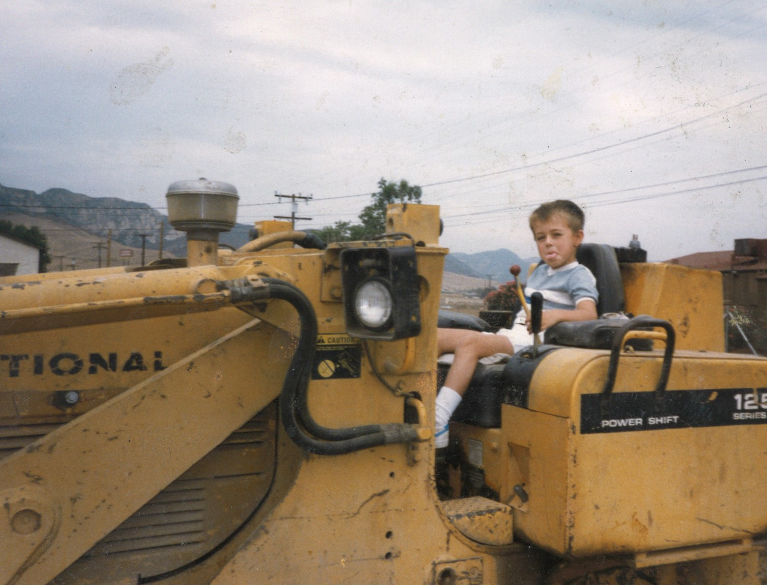 9. Chris sitting on backhoe Castaic Apt - sticking his tongue out.jpg
