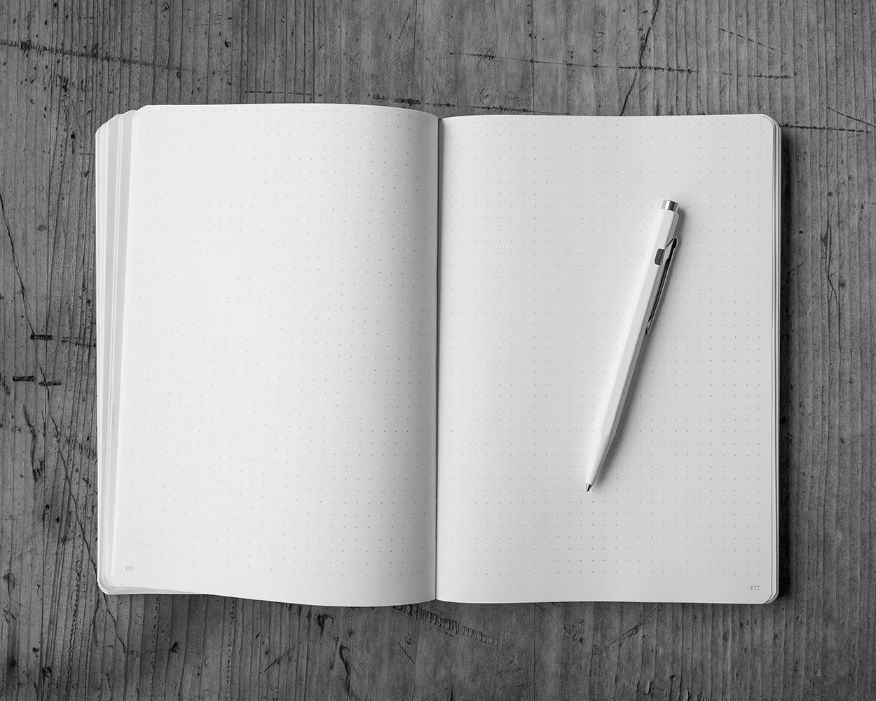 Ein aufgeschlagenes, leeres Notizbuch liegt auf dem Tisch.
