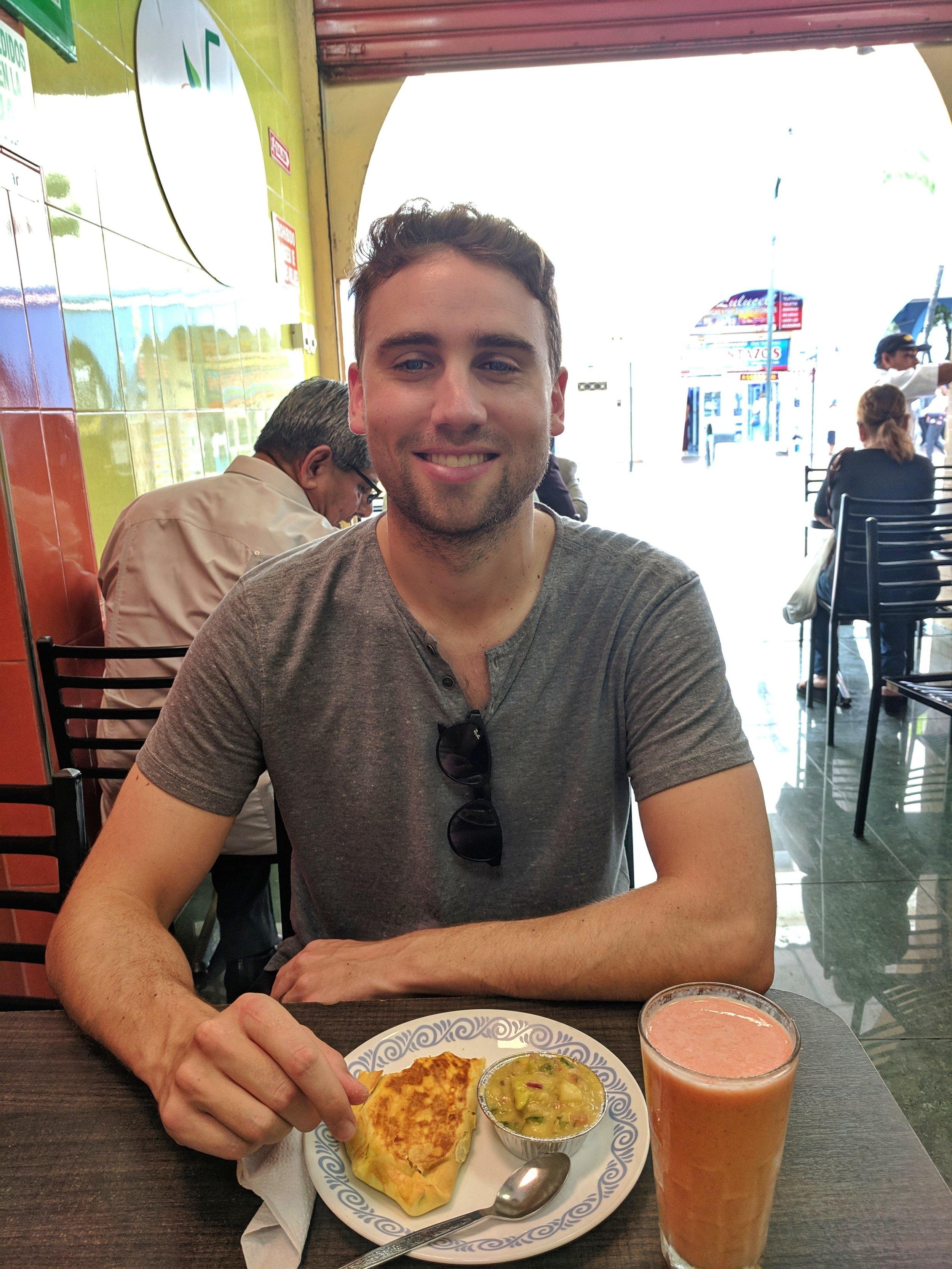 Phil with his chicken empanada and our guava batido (guava, milk, ice & sugar)