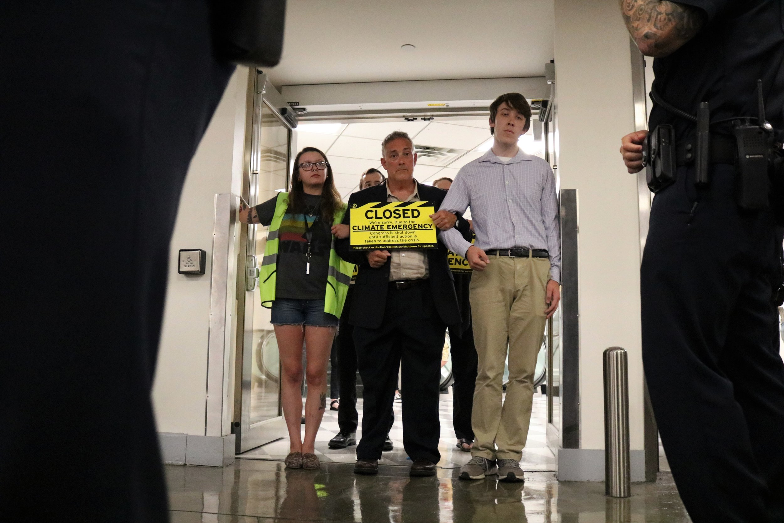 A soft blockade protects protesters glued to the doors, framed by police officers.  Photo: Drew Larsen