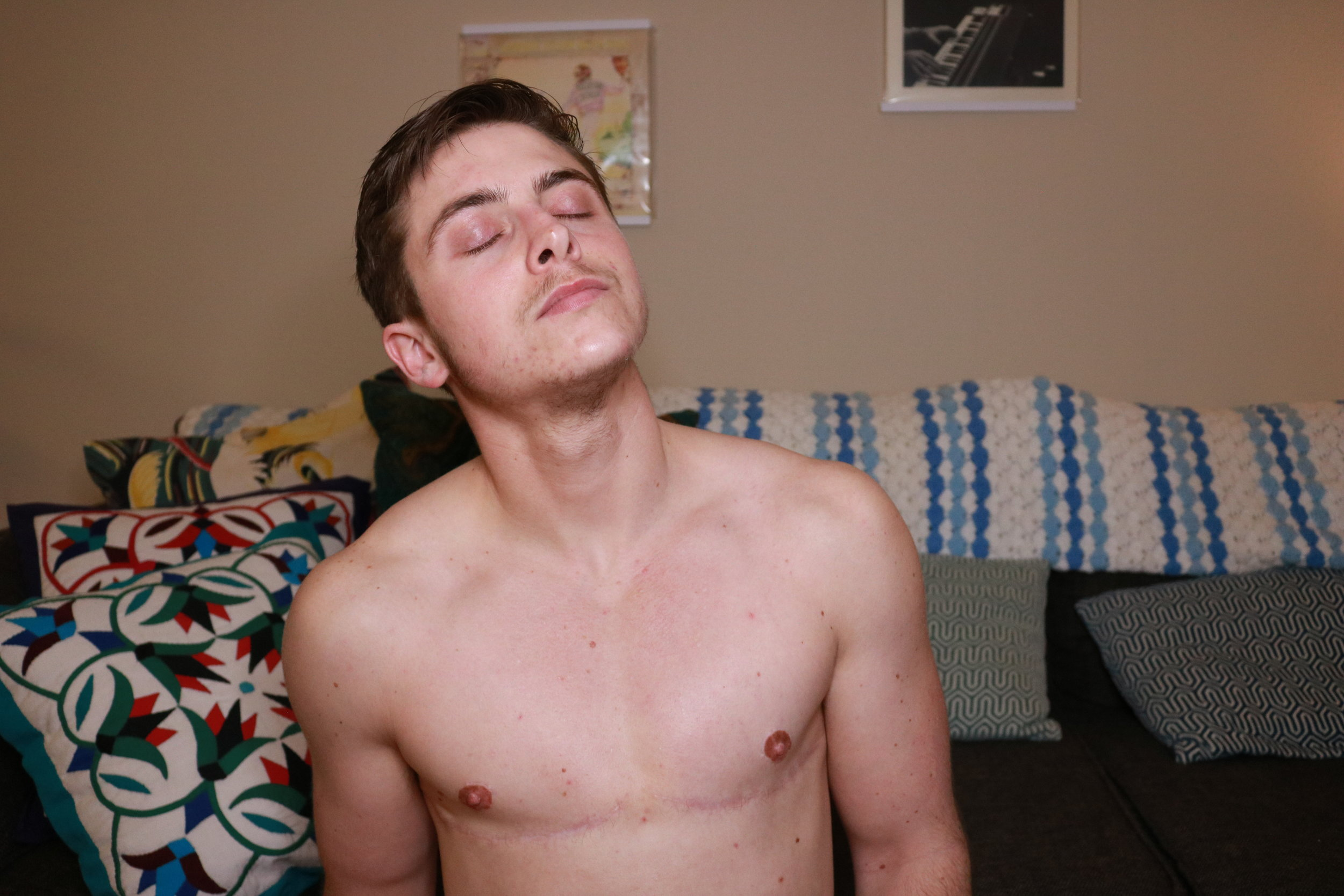 Photo taken by Thomas, in his living room, March 2019. Image Description: Thomas sits shirtless on the floor of his living room in front of his couch covered in colorful pillows and blankets. Album covers hang on the wall behind him as he closes his eyes, stretches his neck, and breathes in a deep breath. His top surgery scars trace thin, pink smiles across his chest.