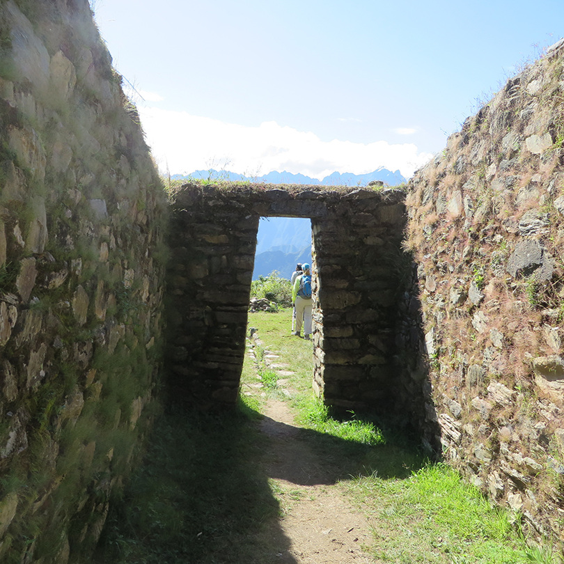 Our first view from the west at a ruin of an Inca rest station. The larger mountains over the top of the arch dwarf Mach Picchu, on the darker ridge over the heads of my fellow travellers.